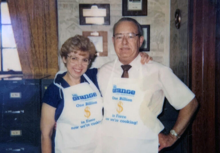Joyce Pipes and Paul Pipes standing in Pipes Insurance Service office with Grange Insurance aprons on